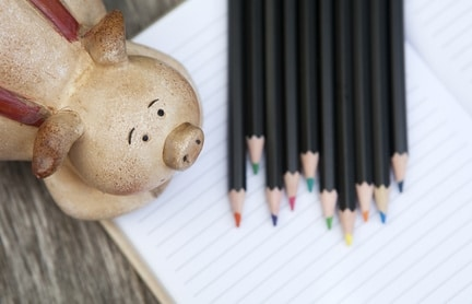 Our website pricing : piggy bank next to coloured pencils