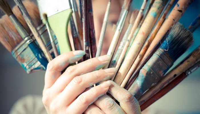 Showing a woman's hands with paint on them holding well-used paintbrushes to illustrate the art of web design