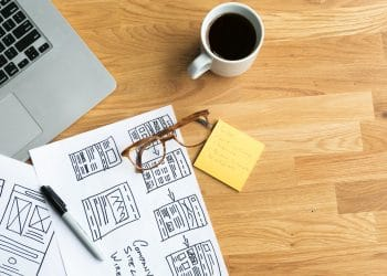 website design services concept - table with notepad glasses and coffee