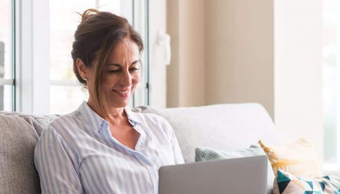 Middle aged woman using laptop in the sofa with a happy face - learning how to update website concept